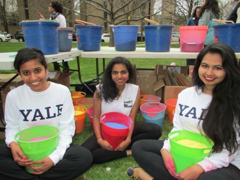 students holding buckets of Holi powder 2015