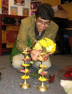 Student arranging flowers on diya for Dasara puja