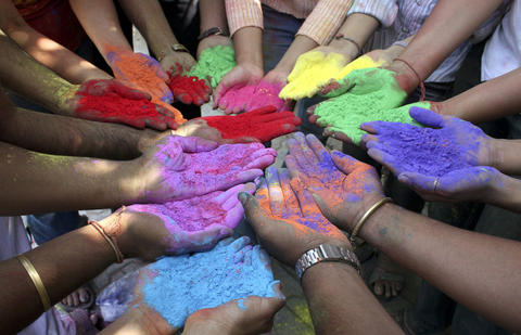 Hands holding colored powders